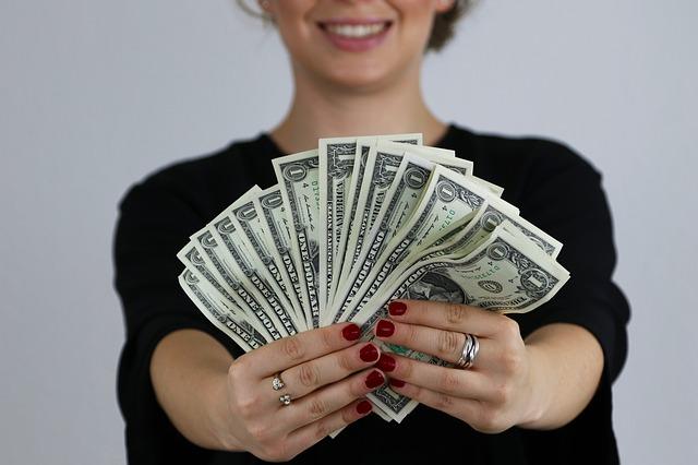 vějíř bankovek v ruce, červené nehty